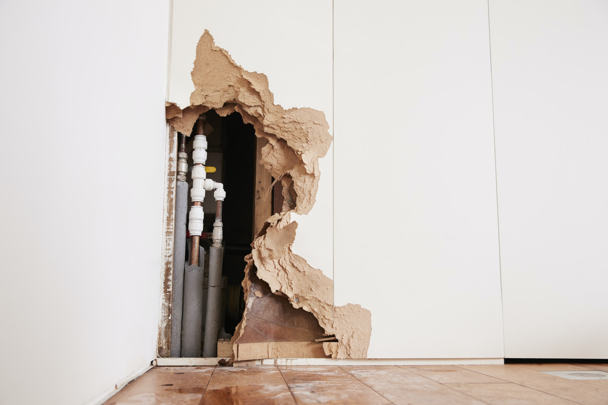 Damaged wall exposing burst water pipes after flood